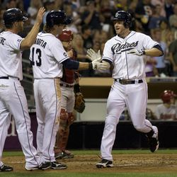 San Diego Padres' Chase Headley, right, is greeted at the plate by teammates Logan Forsythe, left, and Chris Denorfia,second from left, after driving them in on his three-run home run against the Arizona Diamondbacks in the third inning of their baseball game Friday, Sept. 7, 2012, in San Diego. Diamondbacks catcher Miguel Montero watches behind.