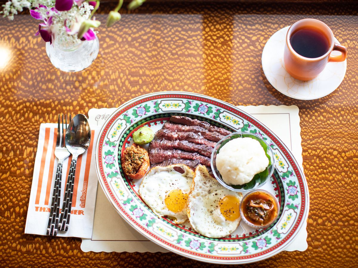 An oval shaped plate with slices of thinly-cut meat, sunny side up eggs, a bowl of steamed white rice, and an orange sauce.