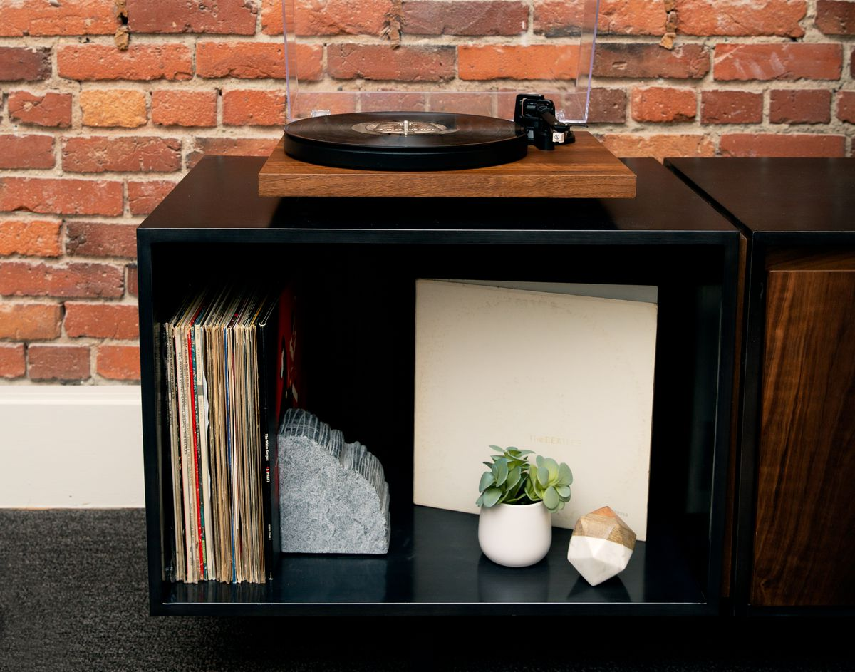 A record cabinet against an exposed brick wall with a turntable on top and records inside.