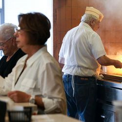 John Katzourakis, right, tends to the broiler as his wife, Rula, second from left, serves customers at Crown Burgers in Salt Lake City on Friday, Aug. 5, 2016. John and Rula Katzourakis have owned and operated Crown Burgers for 38 years.