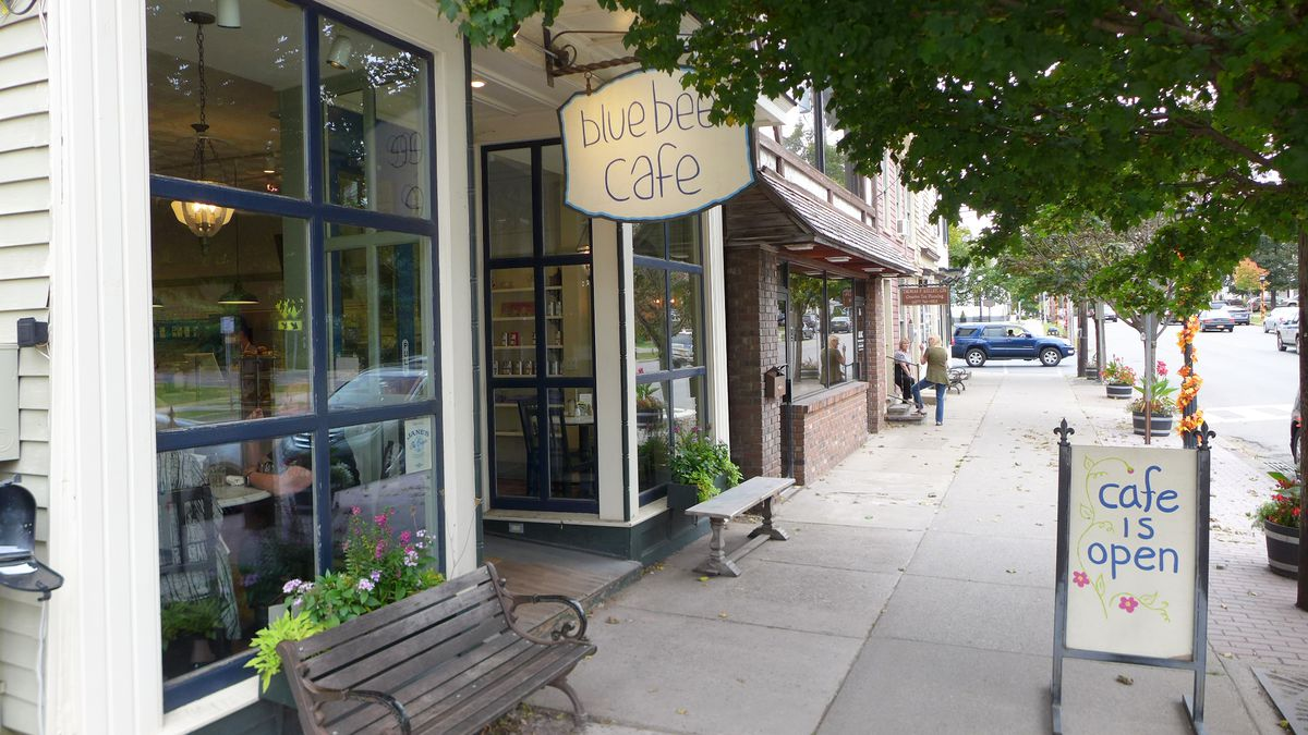 A storefront just with a lit sign above the door that says Blue Bee Cafe and a bench out front...