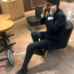 In this photo provided by Georgian Public Broadcaster and photographed by Ketevan Kardava a man speaks on a mobile phone in Brussels Airport in Brussels, Belgium, after explosions were heard Tuesday, March 22, 2016. A developing situation left a number dead in explosions that ripped through the departure hall at Brussels airport Tuesday, police said. All flights were canceled, arriving planes were being diverted and Belgium's terror alert level was raised to maximum, officials said.