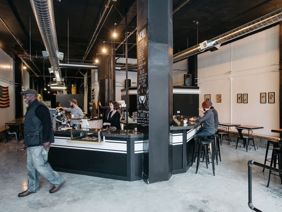 A large industrial coffee shop features a hexagonal  black and white coffee bar at the center of the room.