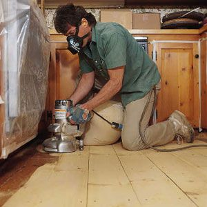 Person using an edger against cabinets and walls.