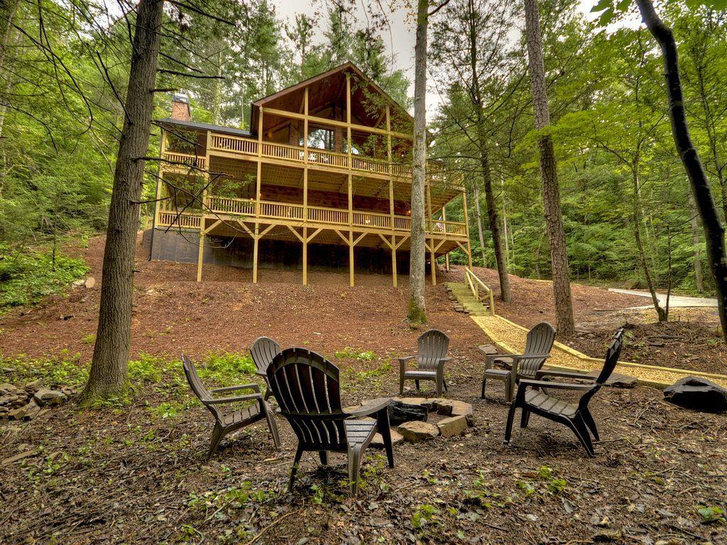 Three-story house in background with firepit and outdoor chairs in the foreground.