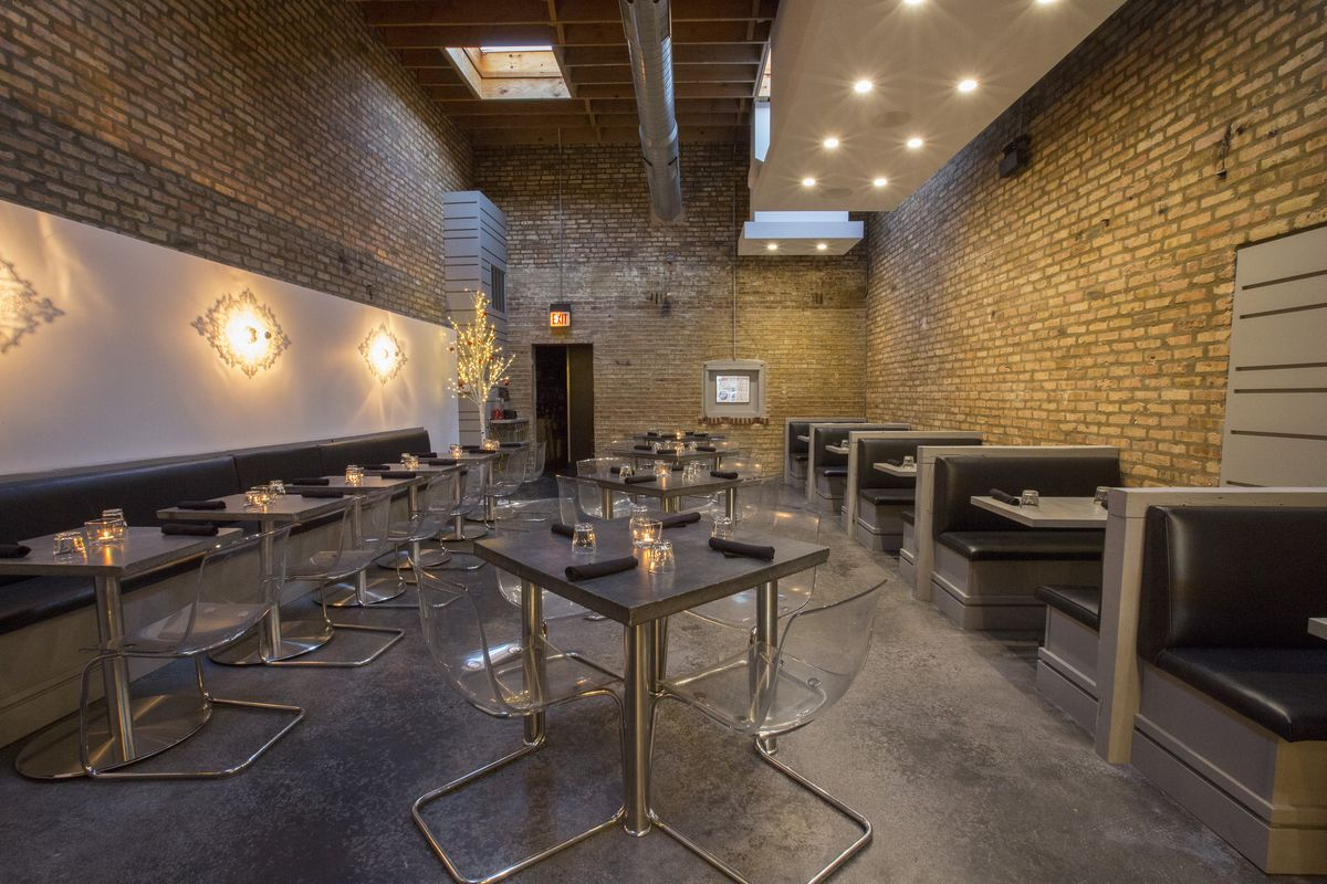A narrow dining room with exposed brick walls and grey tables and chairs.