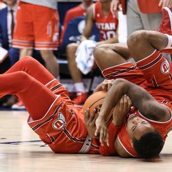 Utah Utes guard Justin Bibbins (1) and guard Sedrick Barefield (0) tumble after fighting for a loose ball with Brigham Young Cougars guard Zac Seljaas (2) at the Marriott Center in Provo on Saturday, Dec. 16, 2017.