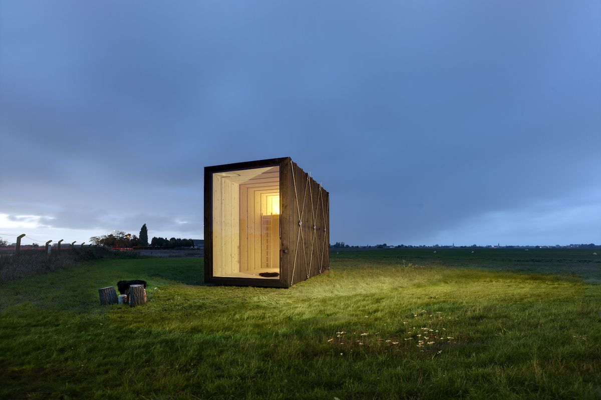 Boxy tiny home sitting in field at dusk.