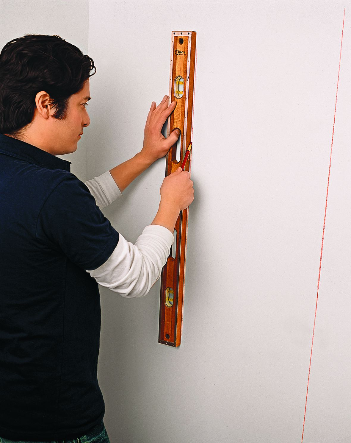 Person measuring wall with a level.