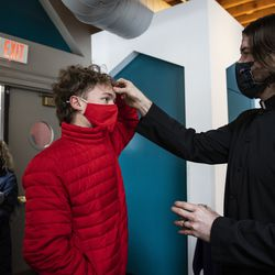 As his mom looks on, Reid Peterson, 16, of the South Loop, receives the imposition of ashes from Pastor Ben Adams at Holy Trinity Lutheran Church in the South Loop on Ash Wednesday, Feb. 17, 2021.