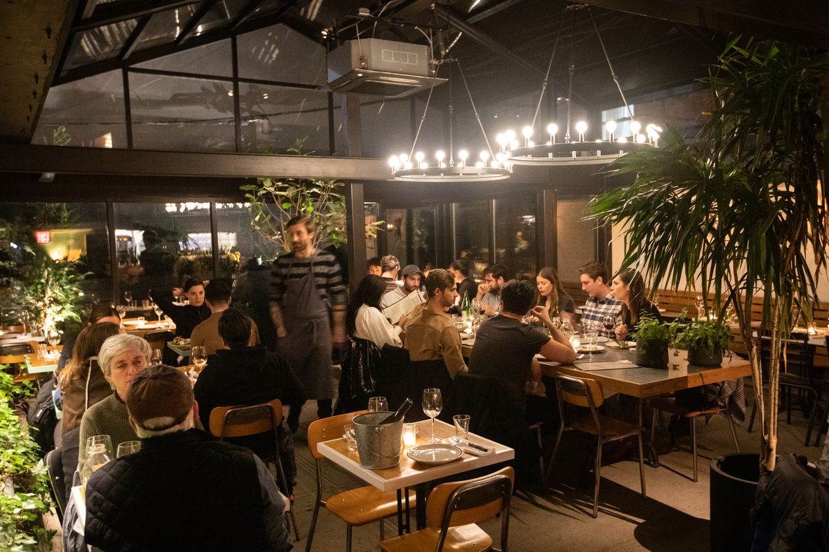 A giant dining room with skylights and black walls with diners scattered here and there.