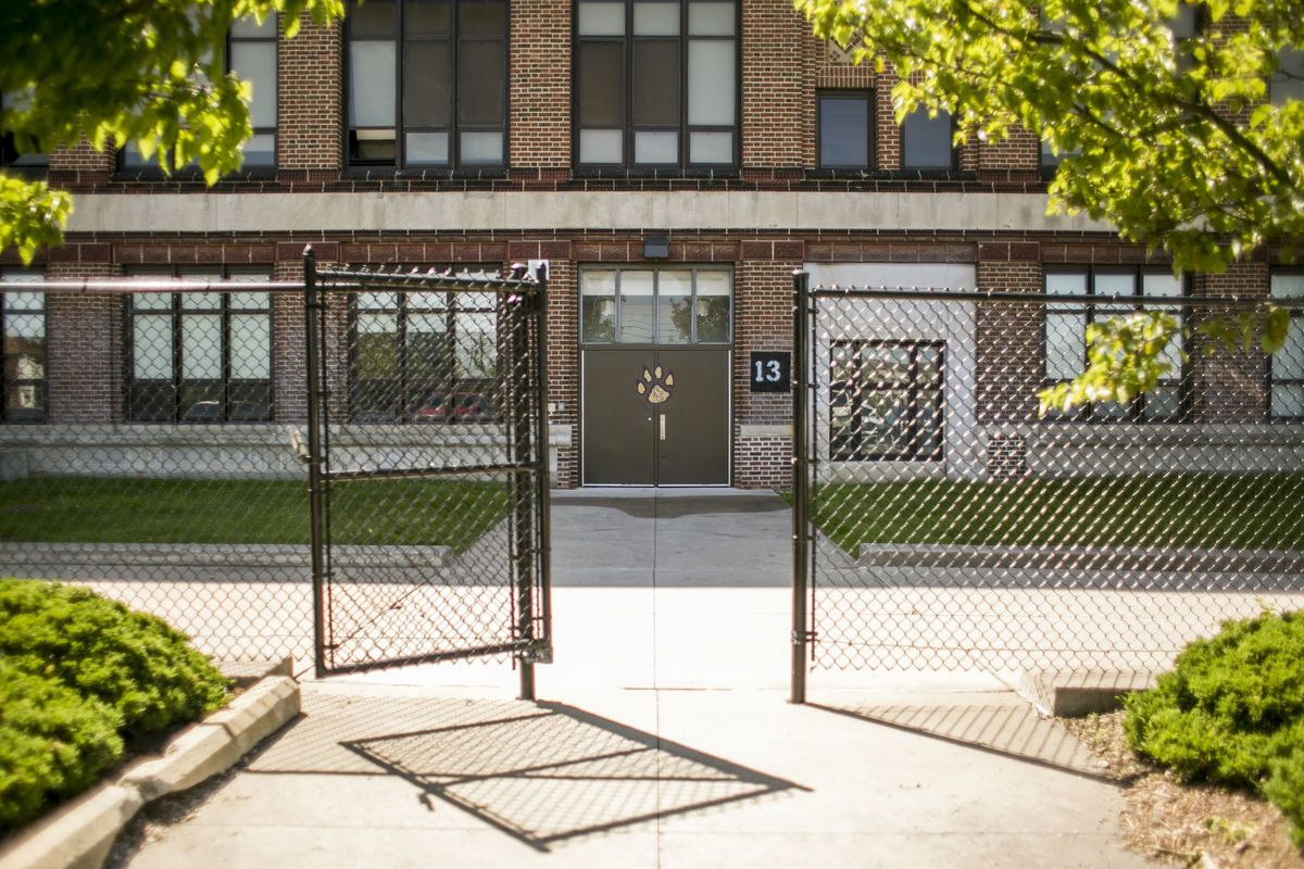 Detroit's Southeastern High School, a large brick building surrounded by a chainlink fence. There is a logo of a yellow paw print on the door.