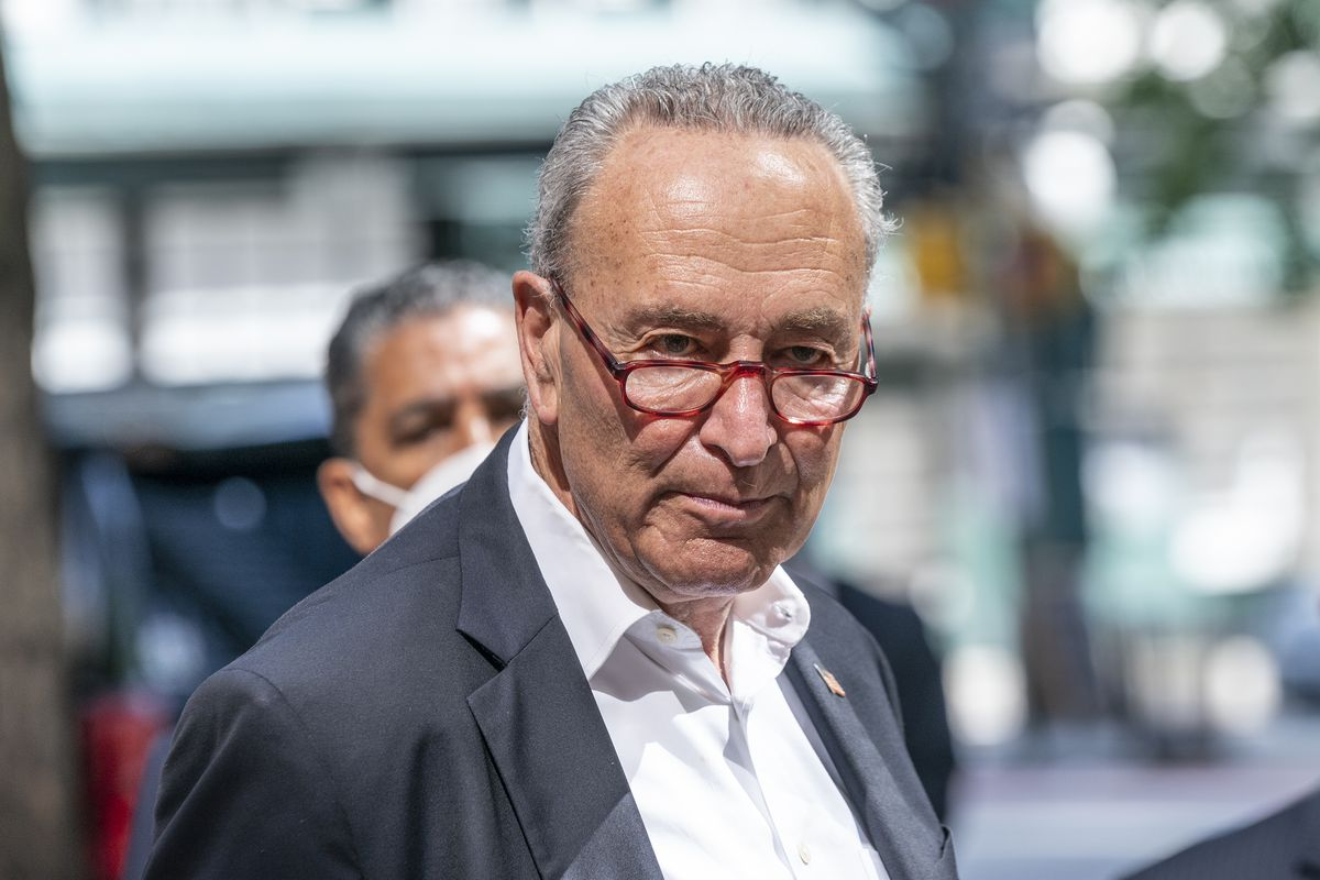Schumer, his red glasses perched on his nose, looks at the camera gravely, standing at a podium in a grey suit and open collared white shirt.