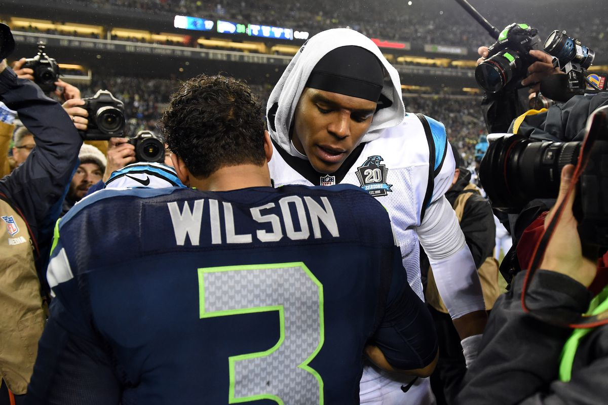 Cam Newton and Russell Wilson hug after their divisional round playoff game