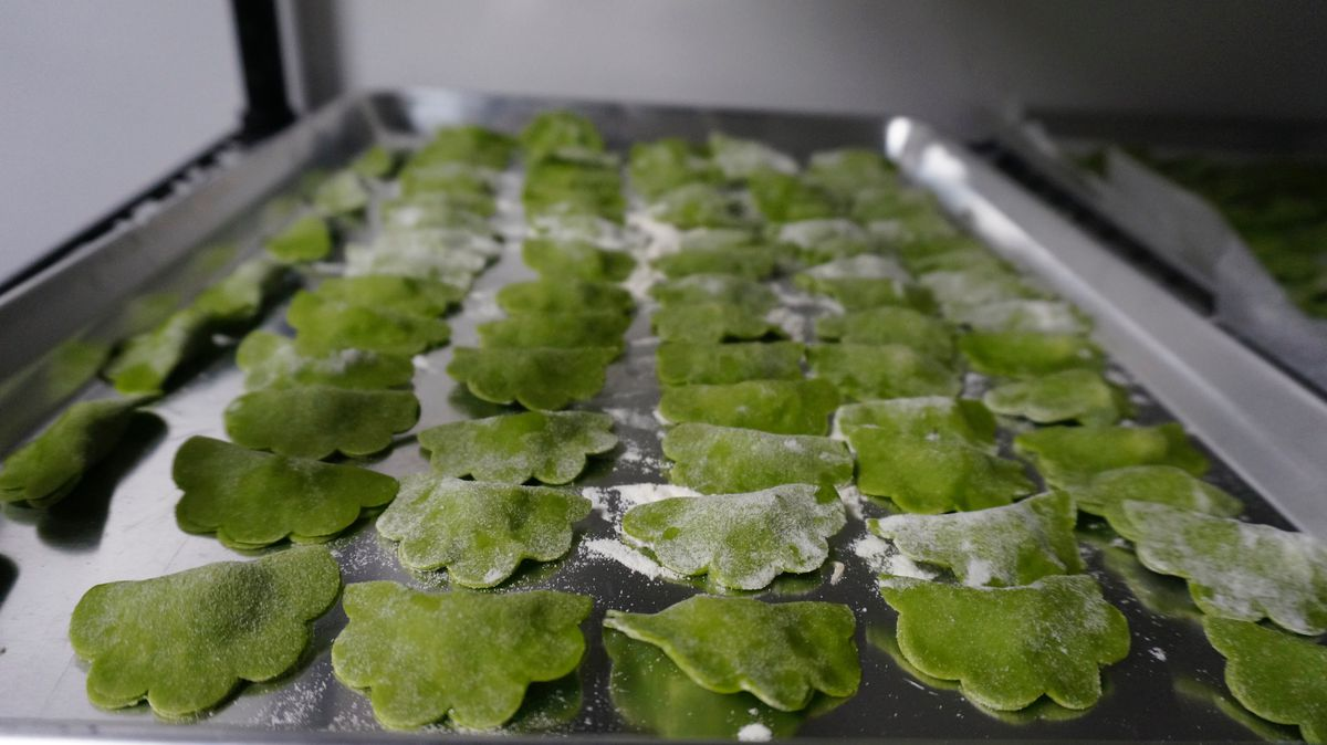 Folded, flower-shaped raviolis are dusted with flour and placed on a baking tray before being cooked