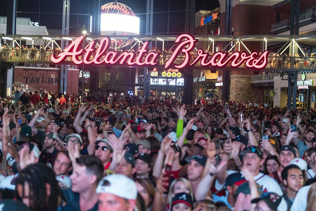 """A large crowd of people standing under a neon """"Atlanta Braves"""" sign."""