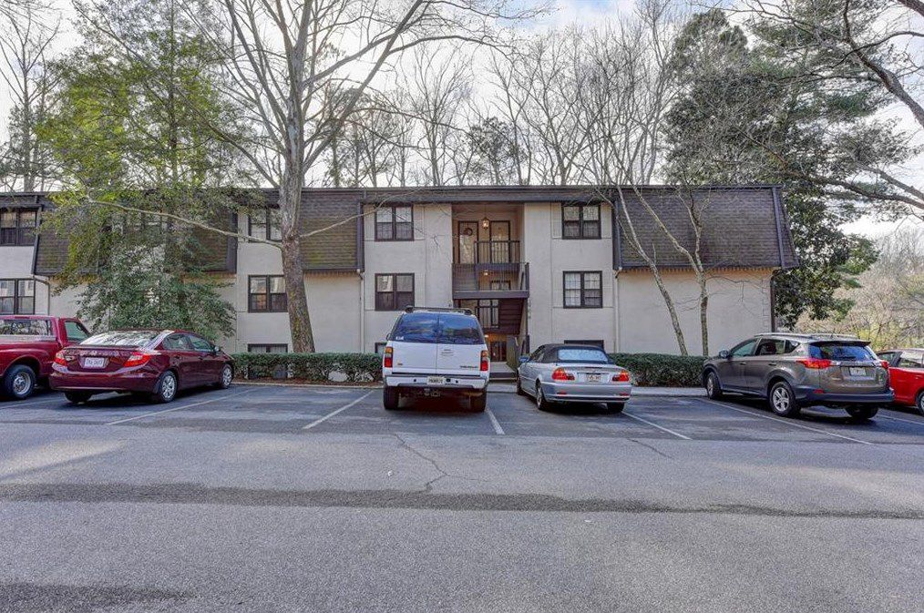 A low-slung apartment complex with cars parked in front.