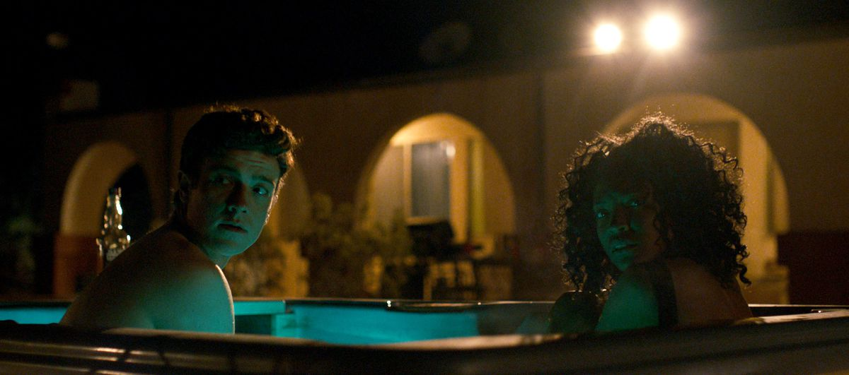 a man and a woman look over their shoulders in a hot tub