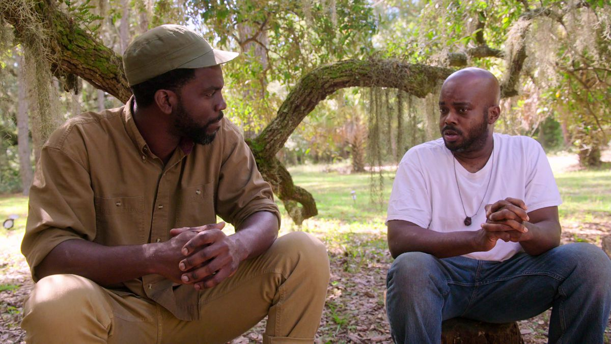 Two men sit on the ground in front of a tree.