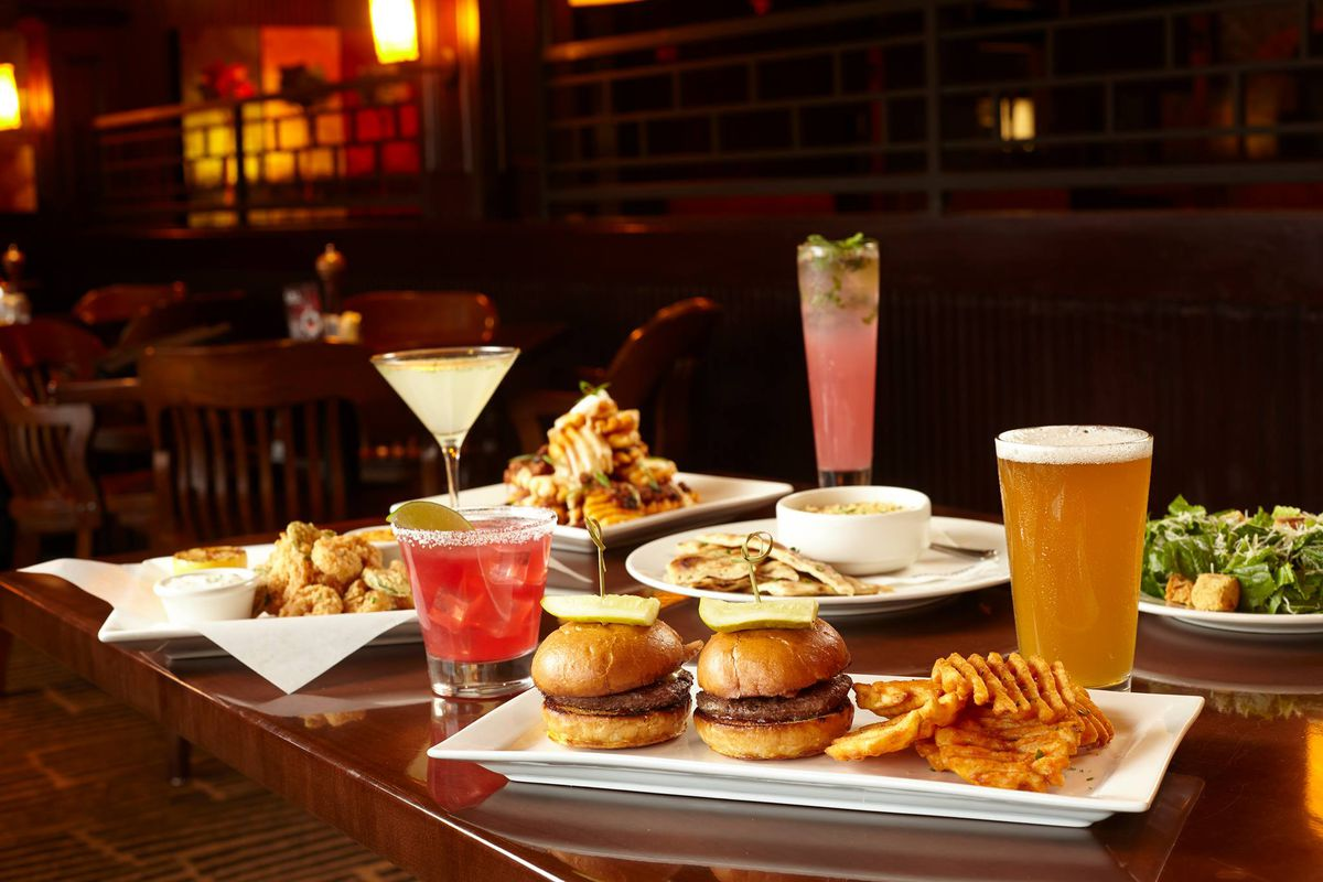 A spread of burgers, beer, salad, and cocktails on a wooden table