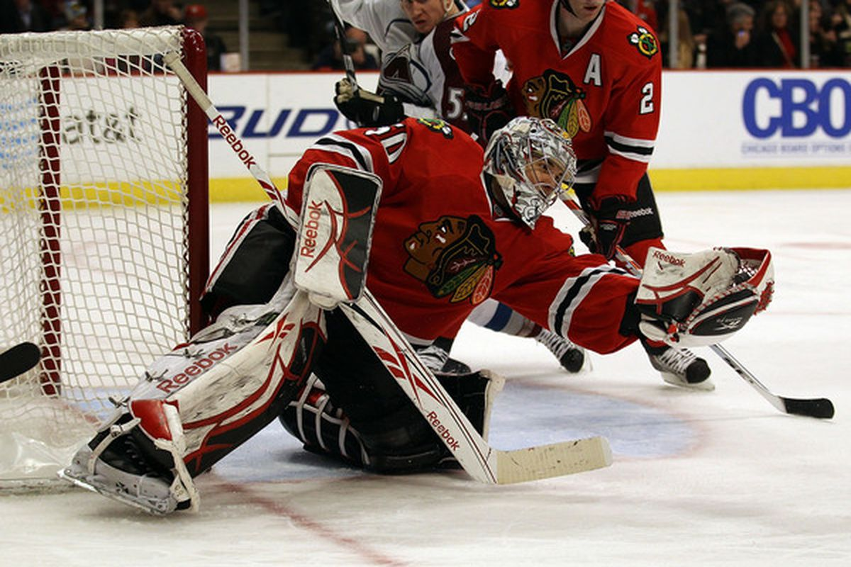 Corey Crawford of the Chicago Blackhawks catches the puck in his glove for a save against the Colorado Avalanche at the United Center on December 15 2010 in Chicago Illinois. (Photo by Jonathan Daniel/Getty Images)