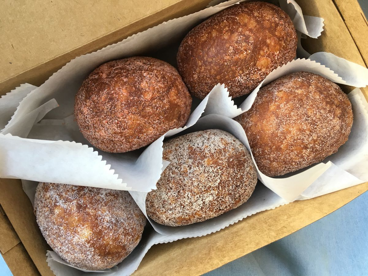 From above, an open cardboard box filled with five dark, sugar-dusted doughnuts separated by paper filling