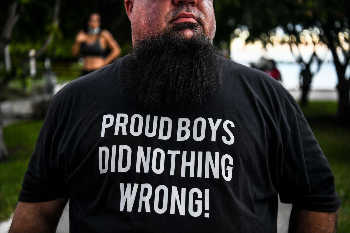 """A man wearing a shirt that says """"Proud Boys did nothing wrong!"""""""