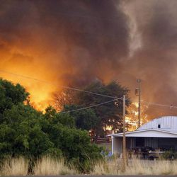 Homes burn as the Yarnell Hill Fire approaches Glenn Ilah on Sunday, June 30, 2013 near Yarnell, Ariz. The fire started Friday and picked up momentum as the area experienced high temperatures, low humidity and windy conditions. It has forced the evacuation of residents in the Peeples Valley area and in the town of Yarnell. (AP Photo/The Arizona Republic, David Kadlubowski)