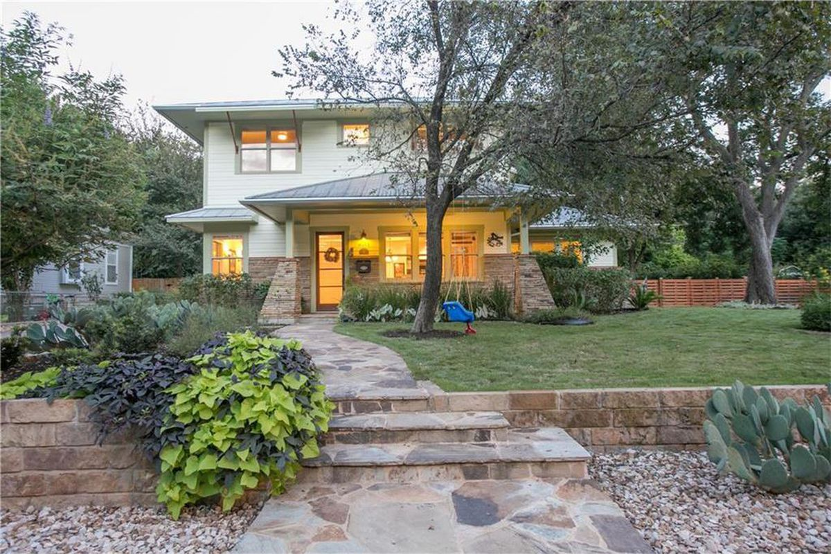 Large Craftsman-style house with stone walkway, trees, lawn