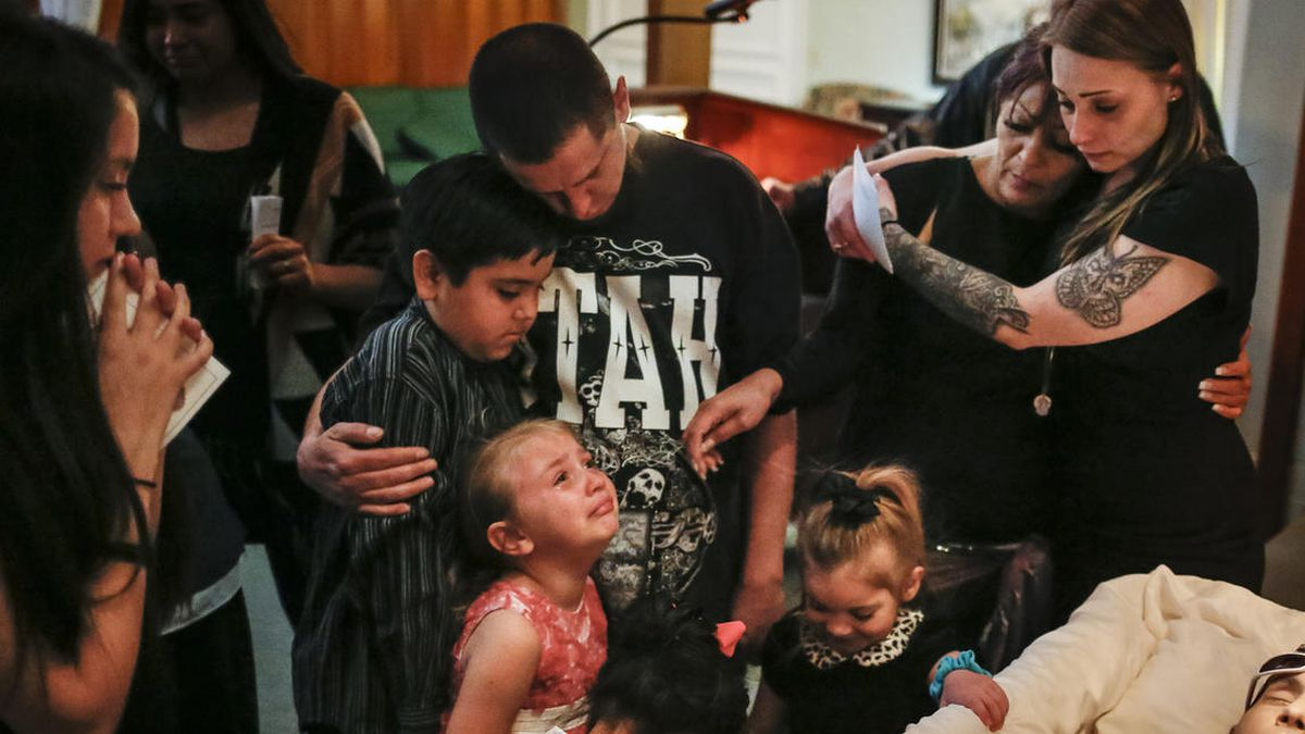Nate Hall, center, embraces his son, Gabriel, while standing with Alizea Gobel, 5, bottom left, her sister, Haze Hall, 4, bottom right, and other family members in front of Matt Hall's casket during his funeral at Myers Mortuary in Ogden on Saturday, Apri