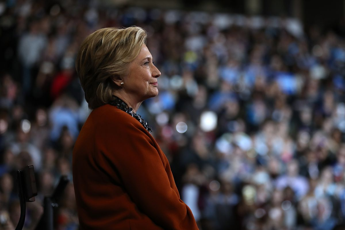 Hillary Clinton looks on as First Lady Michelle Obama speaks during a campaign rally at Wake Forest University