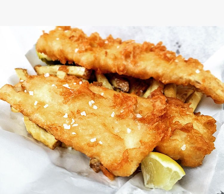 A closeup of two large cod filets with salt crystals on top, set on top a basket of French fries