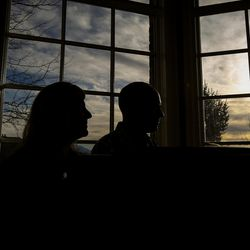 Jon and Michelle Schmidt are silhouetted as they sit and play the piano in their home in Provo on Friday, Nov. 24, 2017.