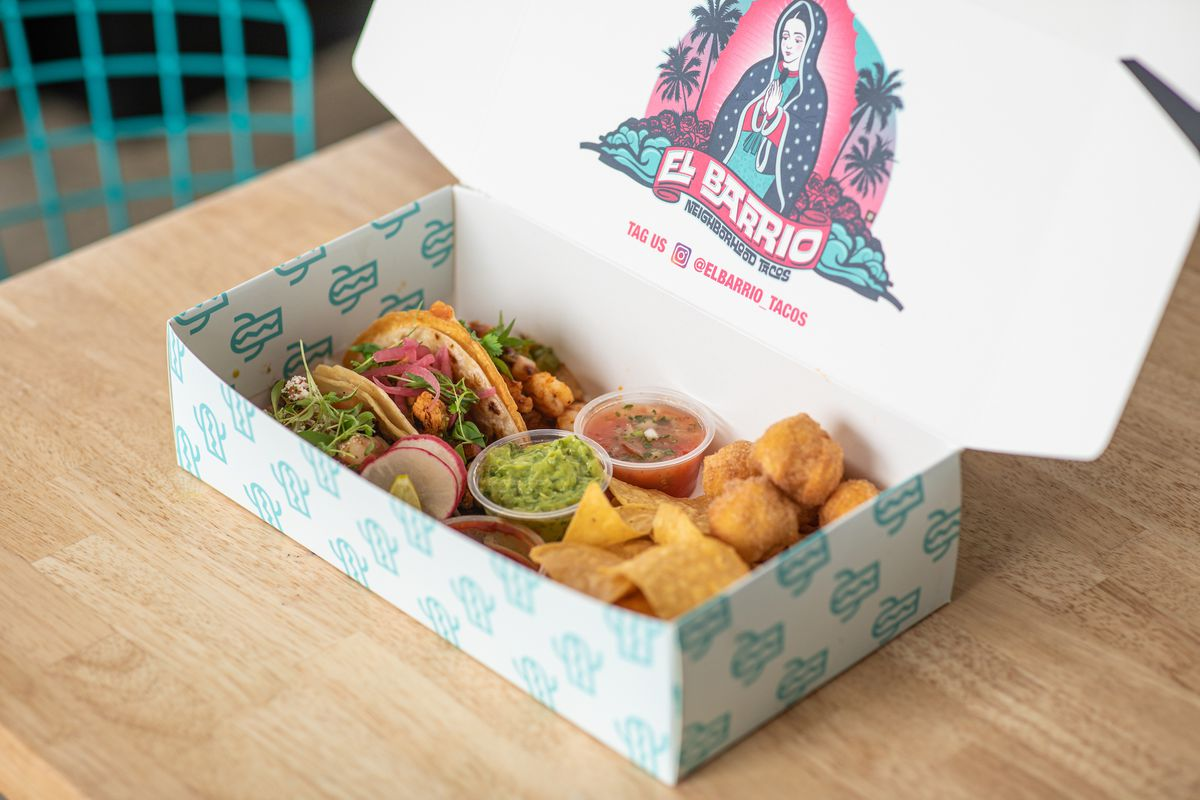 A white box with colorful logo shows two tacos and chips and guac inside.
