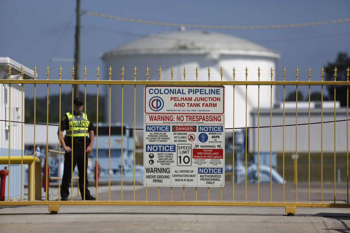 A police officer stands guard outside the Colonial Pipeline's tank farm in Alabama.