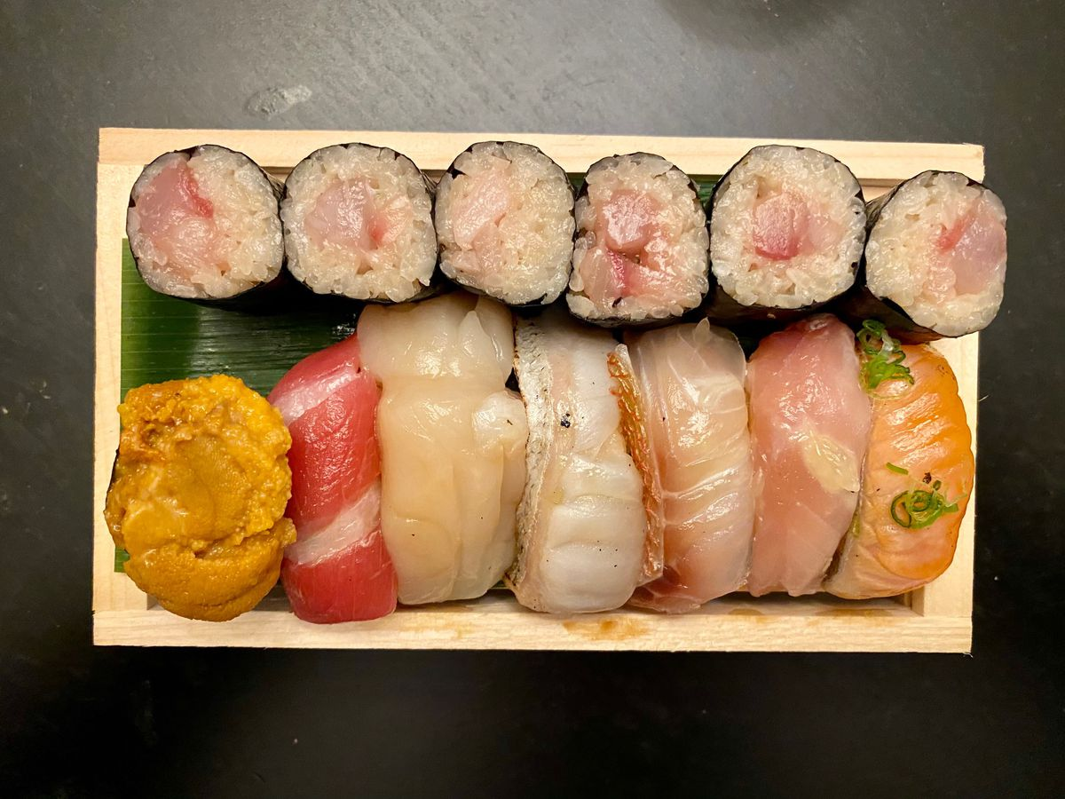 A wooden bento box with various nigiri and a six-piece maki roll