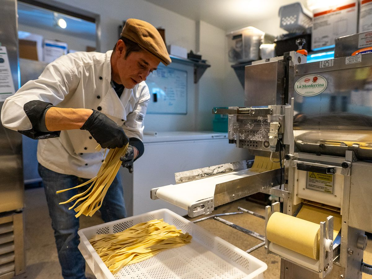 A chef leans over a pasta cutter laying down strips of finished noodles