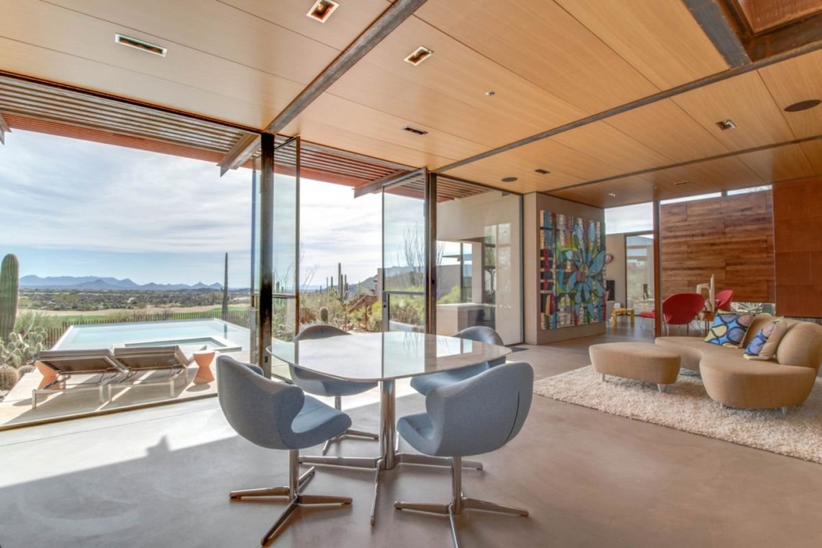 Interior shot of living area opening up to infinity pool and desert landscape via large pivoting glass doors.