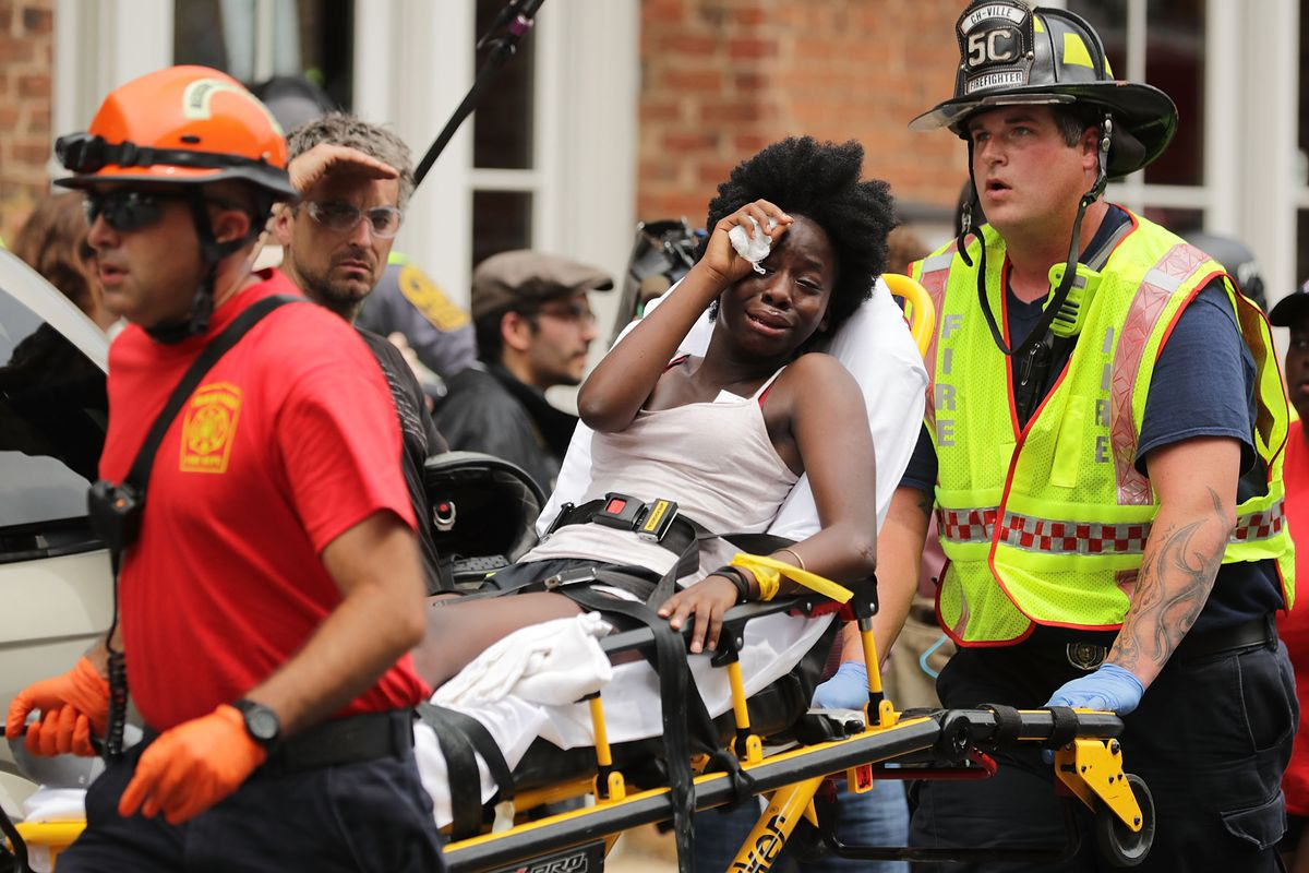 Rescue workers move victims on stretchers after a car plowed through a crowd of counter-demonstrators marching through the downtown shopping district Saturday, in Charlottesville.