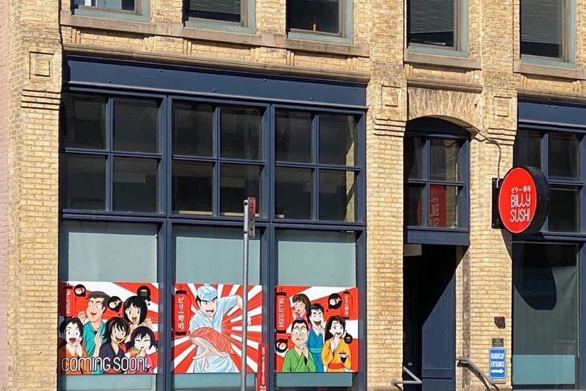 A brick exterior building with a wrap along the windows of sushi anime figures