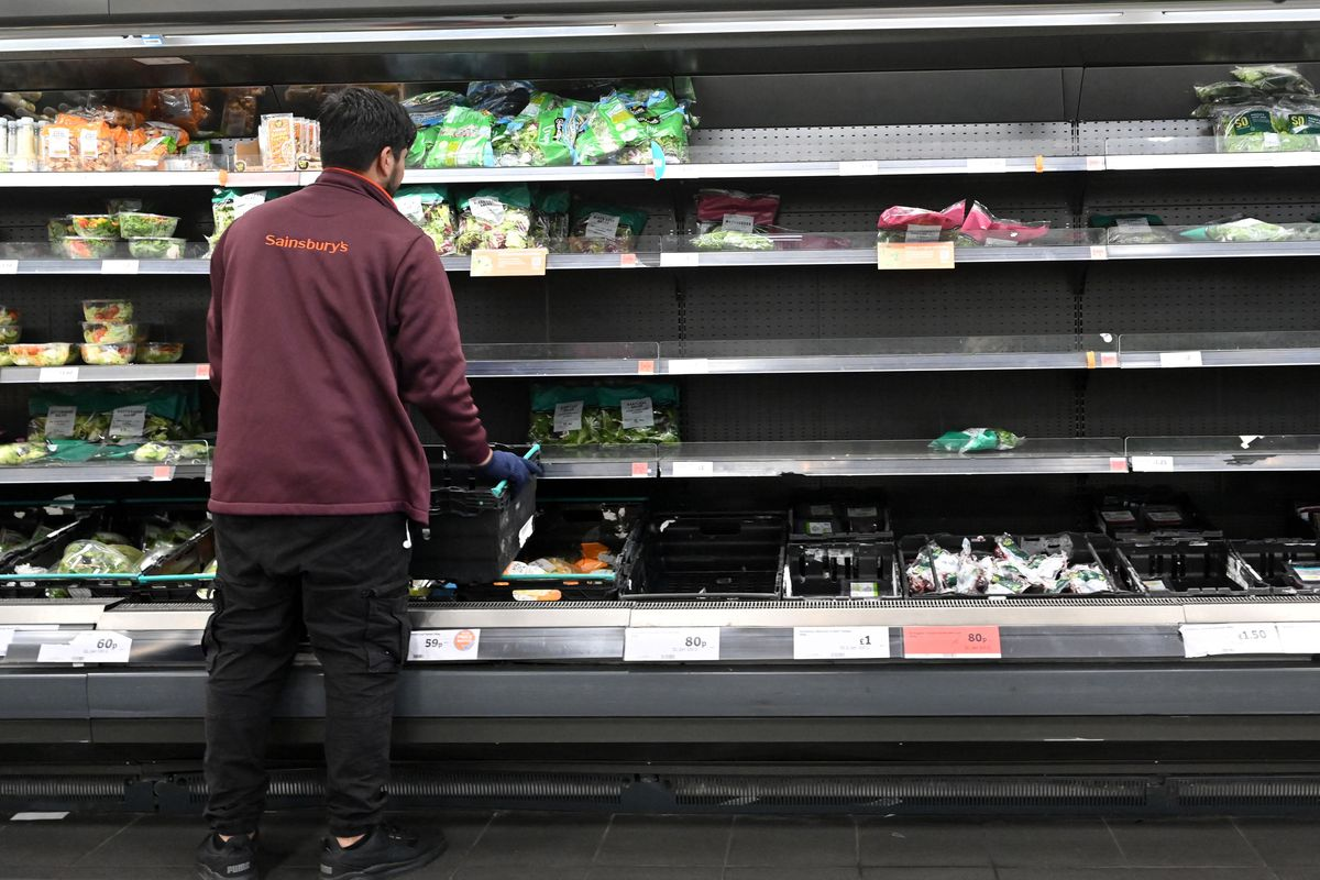 Empty fresh produce shelves at Sainsbury's are tended to by a staff member