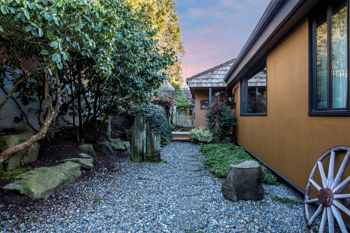 A gravel-based side yard with decorative boulders and a wagon wheel.