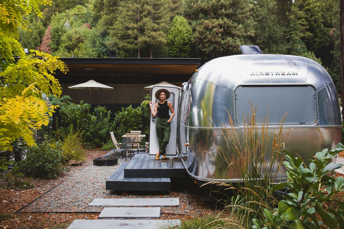 A silver bullet travel trailer by Airstream sits on a raised platform with a deck and landscaping. A woman stands in the trailer's doorway.