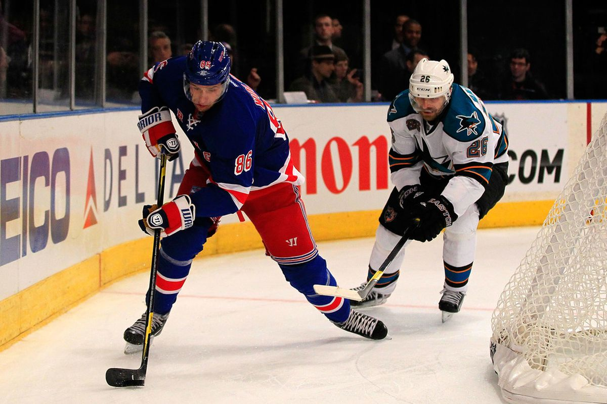 NEW YORK - OCTOBER 31: Wojtek Wolski #86 of the New York Rangers is challenged by Michal Handzus #26 of the San Jose Sharks at Madison Square Garden on October 31, 2011 in New York City.  (Photo by Chris Trotman/Getty Images)