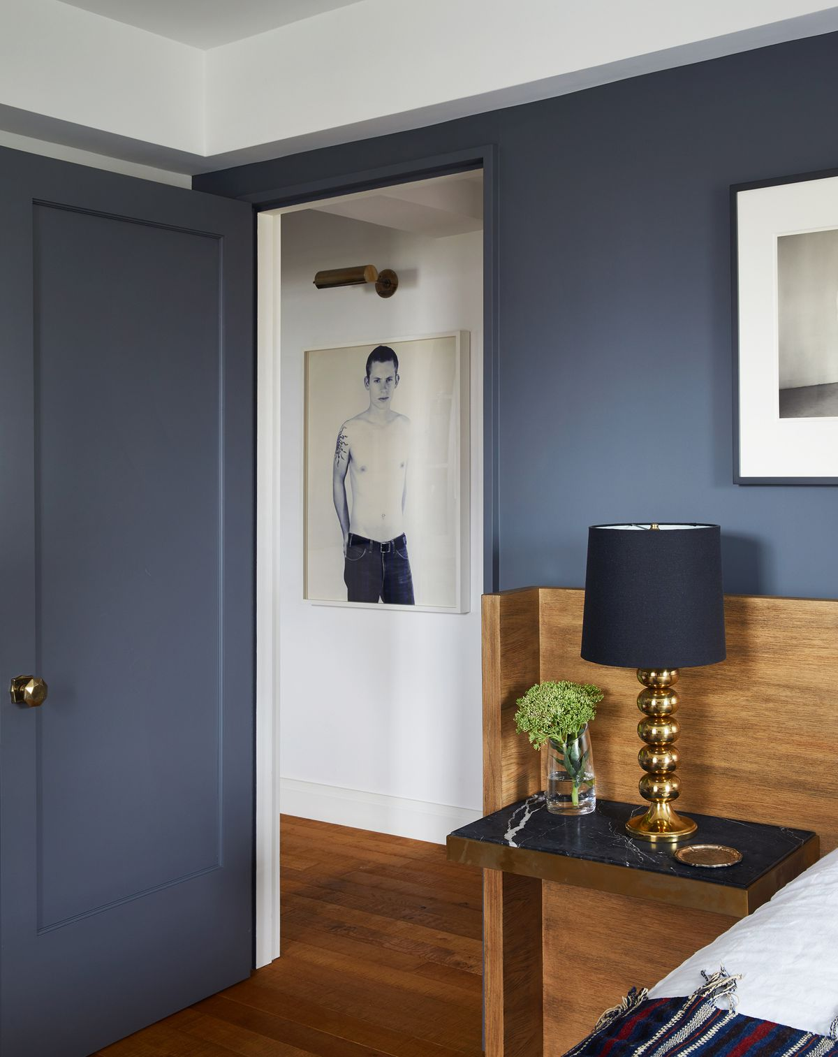 A dark gray bedroom has a wood headboard and white bedding. A black-and-white photo of a shirtless male is visible through the open door.