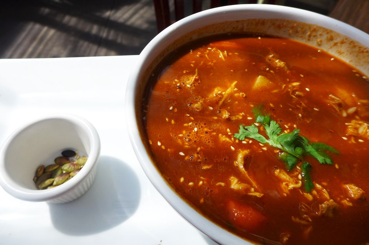 A red soup with shredded chicken visible and a small cup of pumpkin seeds on the side.