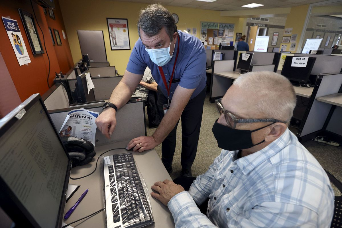 Steve Cline, Department of Workforce Services employment counselor, helps Fred Hansen with his resume at the Department of Workforce Services office in Salt Lake City on Friday, Jan. 22, 2021. The state unemployment rate dropped to 3.6%.
