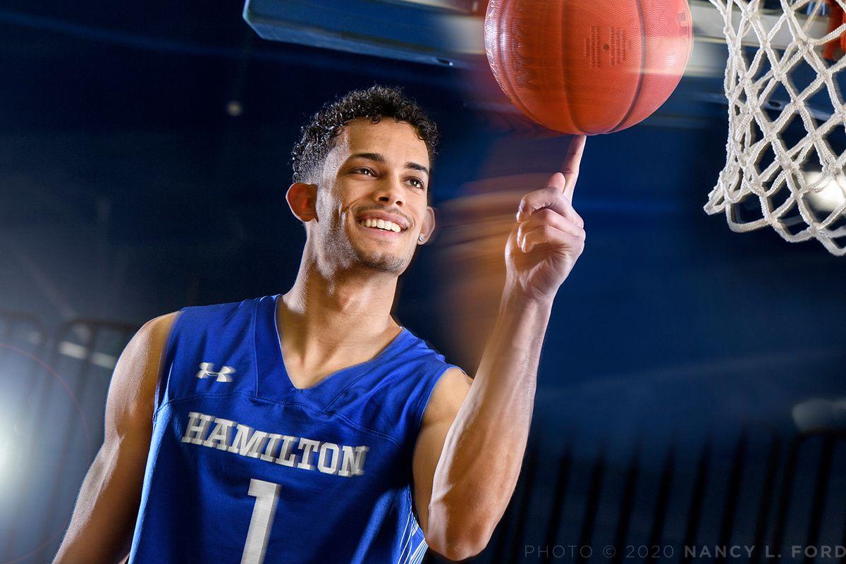 Kena Gilmour spins a basketball on his finger under a basket