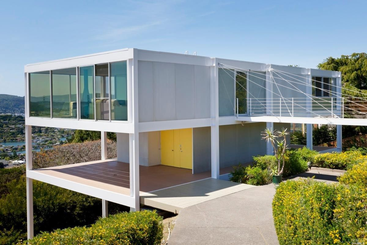 A cubist, flat midcentury home on a hillside with glass walls and a balcony suspended off the back with wires.