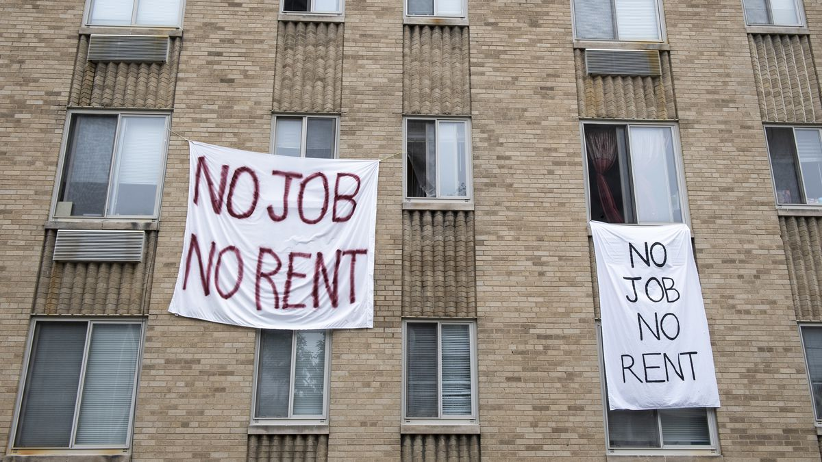 """Two white banners scrawled with, """"No Job No Rent"""" hang from the windows of a brick apartment building."""
